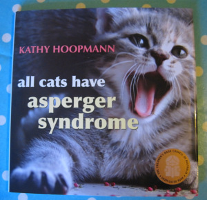 "The front page of the book discussed in this post has a picture of a cat with what could be said is a wide smile and the words ""Kathy Hoopman  All cats have asperger syndrome"""