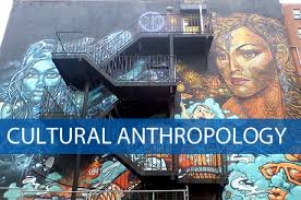 "There is a banner saying ""Cultural Anthropology"" at the bottom of the picture. A set of stairs going up a wall that has a beautiful wall painting of several faces on either side of the stairs."