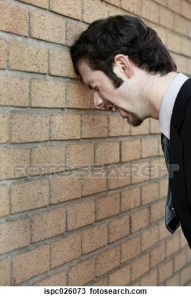 A man  in a suit screaming as he presumably bangs his head against a brick wall